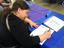 A woman signs a document