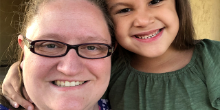 A woman in glasses smiles next to her young daughter