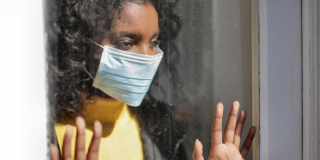 A woman wearing a medical mask looks out a window