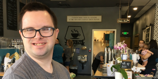 A young man smiles in a coffee shop