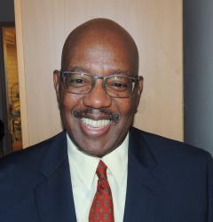 African-American male with dark blue sport coat with a white shirt and red tie
